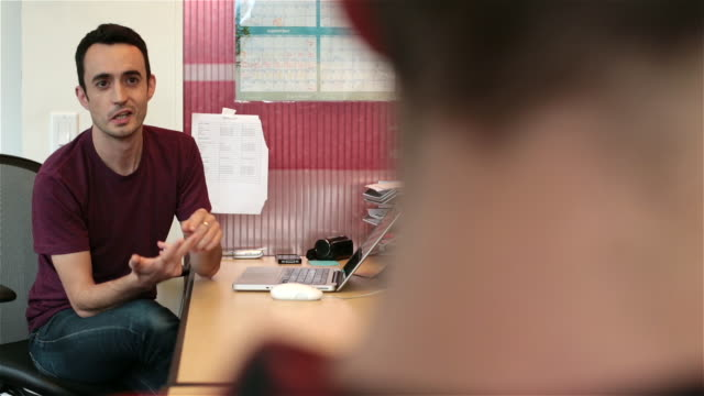 Male coworker lists off options on fingers for trendy young businessman