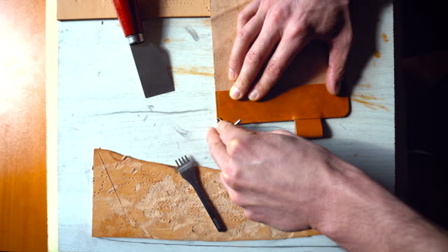 Male crafts-person working on leather case