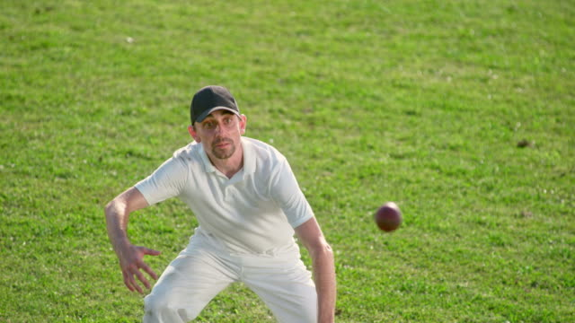 slo mo male cricket player catching the cricket ball with his bare hands - cap stock videos & royalty-free footage