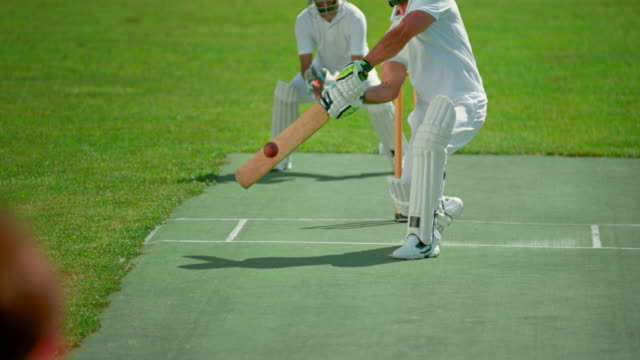 slo mo male cricket player striking the ball with his cricket bat on the sunny playing field - cricket video stock e b–roll