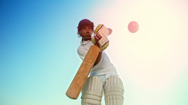 slo mo male cricket player wearing protective gear and hitting the ball in sunshine - cricket ball stock videos & royalty-free footage