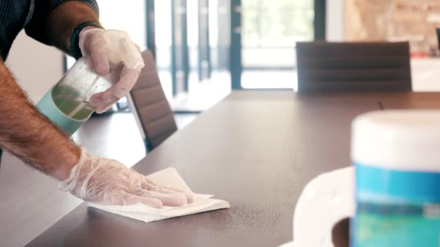 il custode maschio pulisce il tavolo in ufficio durante la pandemia di covid-19 - desk video stock e b–roll