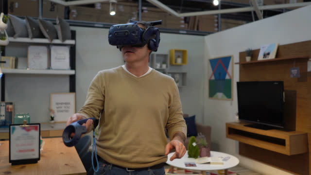 male customer at a furniture store doing a virtual reality tour with a headset - cyberspace stock videos & royalty-free footage