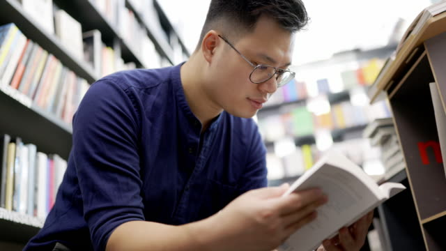 male customer choosing a book to purchase at bookstore - korean ethnicity stock videos & royalty-free footage