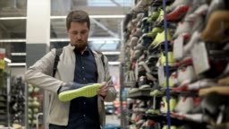 Male customer is taking sport shoes from rack in a sport