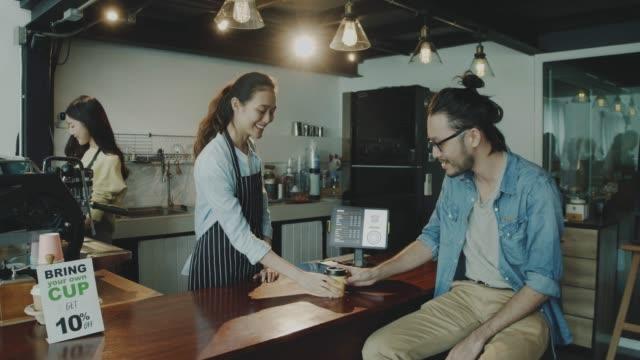 vídeos de stock, filmes e b-roll de cliente masculino que faz a ordem café e pagamento através do cartão de crédito na barra contrária no café com a mulher nova do barista. barista segurando cartão de crédito máquina de leitura e serviço cliente com conveniente. - machine part