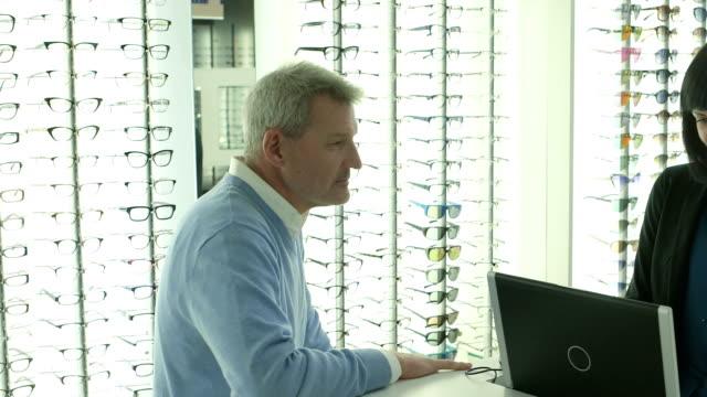 male customer purchases a pair of glasses in optician shop. - mindre än 10 sekunder bildbanksvideor och videomaterial från bakom kulisserna