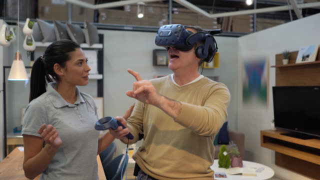 male customer trying out a virtual reality headset doing a virtual tour at a furniture home store and sales clerk standing next to him - virtual reality stock videos & royalty-free footage