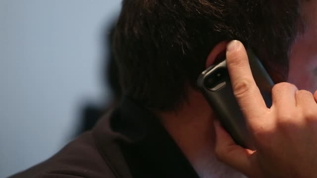 A male customer uses a smartphone mobile device in London UK on Friday April 25 Side view a man speaks on a mobile handset A customer uses a laptop...