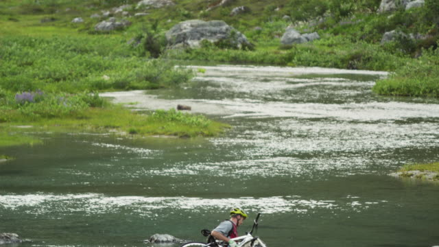 WS TD Male cyclist crossing Alpine river, carrying mountain bikes, Coast Mountains, Squamish, British Columbia, Canada