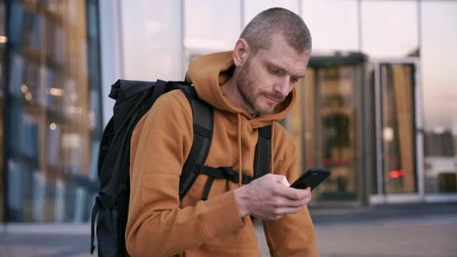 stockvideo's en b-roll-footage met een mannelijke fietser in een rode hoodie en het dragen van een rugzak houdt een telefoon en het typen - ten voeten uit