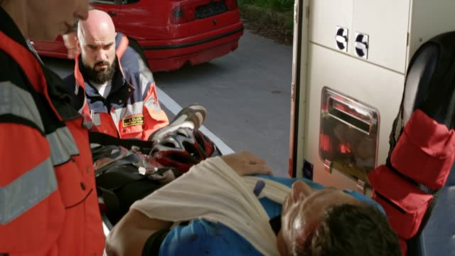male cyclist injured in a accident being loaded into the ambulance on a stretcher - stretcher stock videos & royalty-free footage