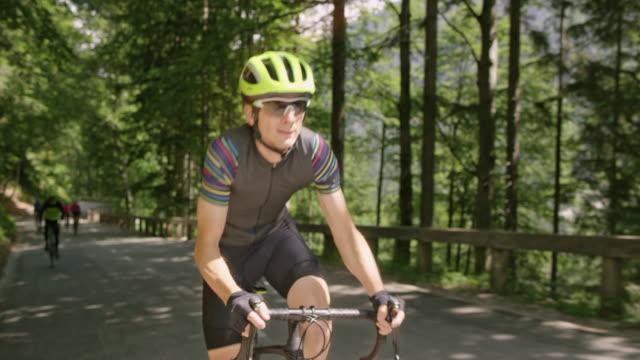 他のサイクリストを残して道をスピードを拾う男性サイクリスト - sunglasses点の映像素材/bロール