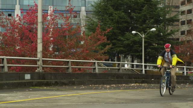 ws male cyclist riding bicycle on bridge / portland, oregon, usa - helm stock-videos und b-roll-filmmaterial