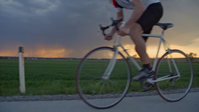 stockvideo's en b-roll-footage met ms male wielrenner fietsten op landelijke weg met storm wolken in de achtergrond - train vehicle