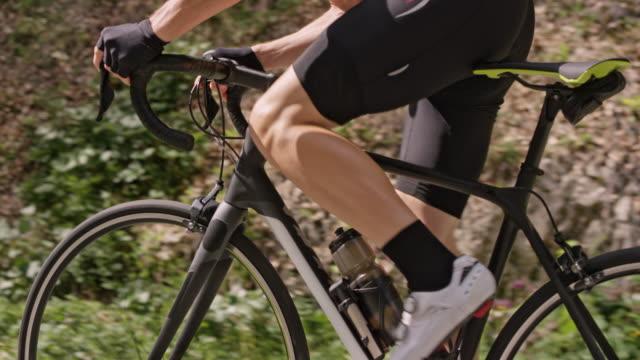 slo mo manliga cyklist ridning hans väg cykel upp en väg i naturen - landsväg bildbanksvideor och videomaterial från bakom kulisserna