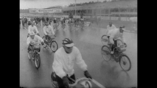 male cyclists line up at start of race / start flag lowered and bikes start to move / two men teams with front one riding a low power motorbike and... - バーデン・ビュルテンベルク州点の映像素材/bロール