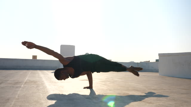 ms male dancer balancing body on one hand while performing on rooftop - tights stock videos & royalty-free footage