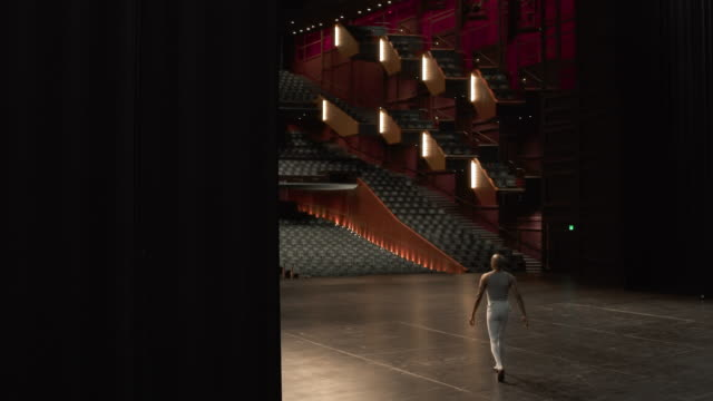 Male dancer entering stage and rehearsing ballet dance.