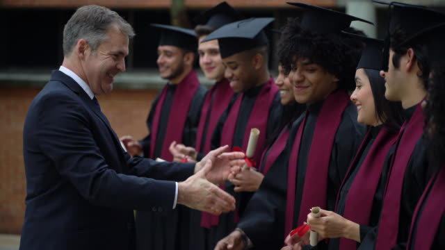 male dean of the university handshaking new graduates very cheerfully and smiling - diploma video stock e b–roll