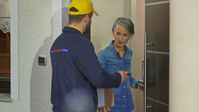 女性にパッケージを届ける男性配達サービスワーカー - 受ける点の映像素材/bロール