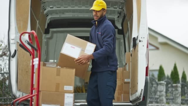 male delivery service worker placing packages from the van onto the cart - furgone video stock e b–roll