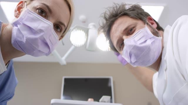 vídeos de stock, filmes e b-roll de pov masculino dentista e seu assistente, olhando para o paciente na cadeira odontológica - saúde dental