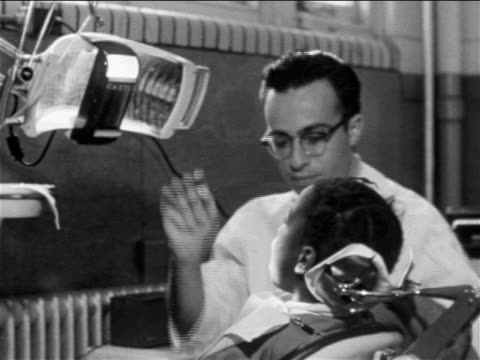 B/W 1955 male dentist examining mouth of Black girl in dentist's chair / Philadelphia / travelogue