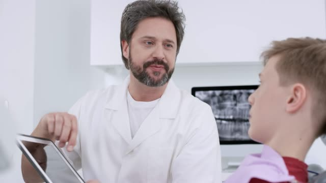 male dentist using the digital tablet to show his young male patient the health of his teeth - lab coat stock videos & royalty-free footage