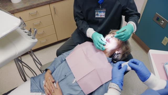 a male dentist wearing an n95 mask adjusts his dental light above a female patient in her sixties who removes her face masks as she lies in a dentist's chair in the examination room of a dental clinic as a dental hygienist assists - dentist stock videos & royalty-free footage