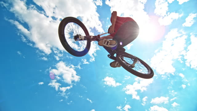 slo mo male dirt jump biker jumping high into the clear blue sky - jump shot stock videos and b-roll footage