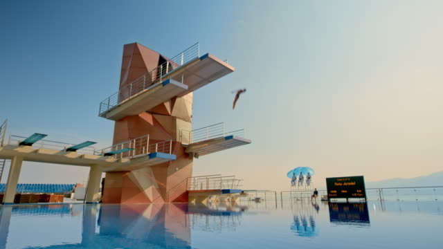 cs male diver jumping from the highest platform into the calm pool and rotating in the air before landing in the water - tuffarsi video stock e b–roll