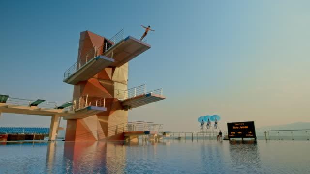 vídeos de stock, filmes e b-roll de mergulhador de cs macho saltar da plataforma de mergulho mais alta em uma competição em sol poente - escrita ocidental