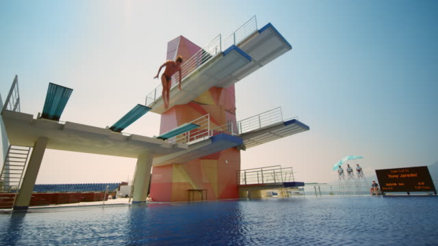cs male diver jumping off the spring board, rotating in the air and diving into the pool at a competition - crane shot stock videos & royalty-free footage