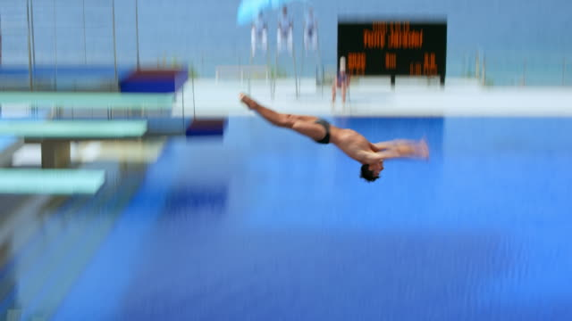 male diver rotating and diving into the pool at a competition on a sunny day - scrittura occidentale video stock e b–roll