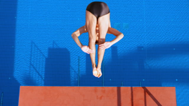 slo mo cs male diver standing at the edge of the platform in sunshine and diving into the pool with rotation - diving platform stock videos and b-roll footage