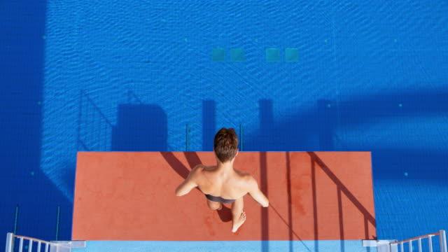 vídeos y material grabado en eventos de stock de slo mo cs hombre buzo caminar al borde de la plataforma de buceo mirando hacia la piscina y concentración - en el borde