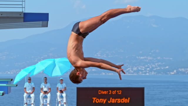 slo mo male diver straightening his body in the air before hitting the pool at a diving competition - diving platform stock videos and b-roll footage