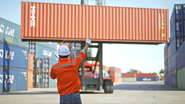 4k male dock worker using a radio telling top handler moving containers in shipping dock - crane stock videos & royalty-free footage
