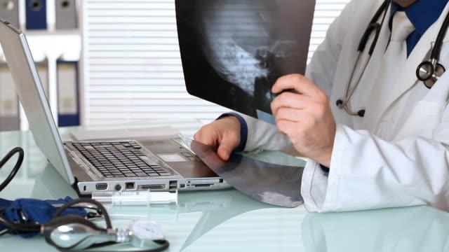 vídeos de stock, filmes e b-roll de masculino médico análise de imagens de raio-x no consultório médico - analisando