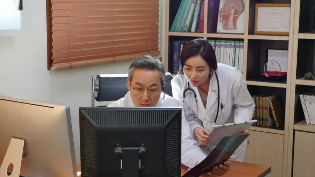 vídeos de stock e filmes b-roll de a male doctor and a female doctor having a conversation - telefone sem fio
