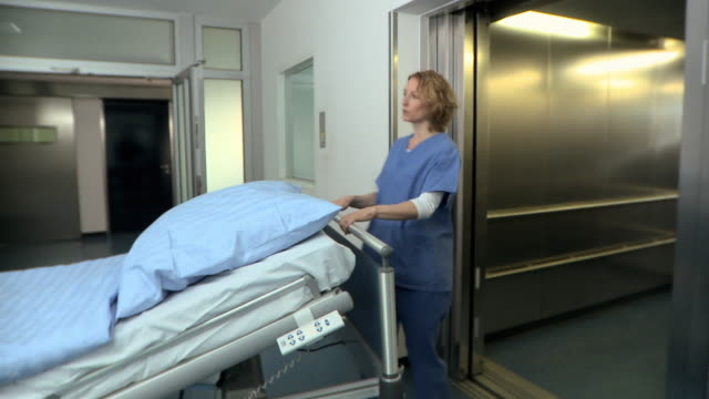 MS, Male doctor and female surgeon pushing hospital bed into elevator, Berlin, Germany