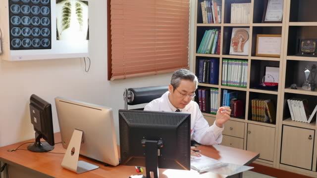 vídeos de stock e filmes b-roll de male doctor consulting a patient on the phone - telefone sem fio