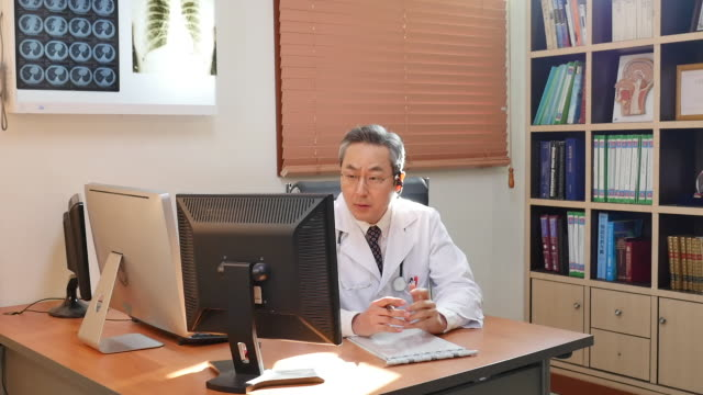 male doctor consulting a patient on the phone - schnurloses telefon stock-videos und b-roll-filmmaterial