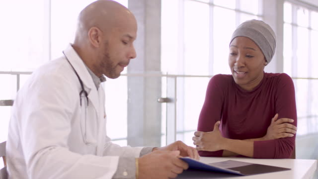 ethnic male doctor consulting with female cancer patient - fatcamera stock videos and b-roll footage