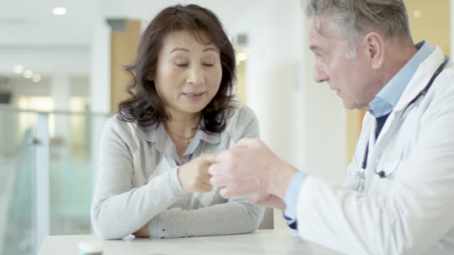 糖尿病を持つ彼の民族のシニア女性患者と相談する男性医師 - 人間の消化器官点の映像素材/bロール