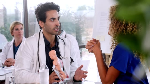 male doctor examines human body model with female colleague - medical student stock videos and b-roll footage