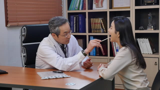 male doctor examining the mouth a female patient - larynx stock videos & royalty-free footage