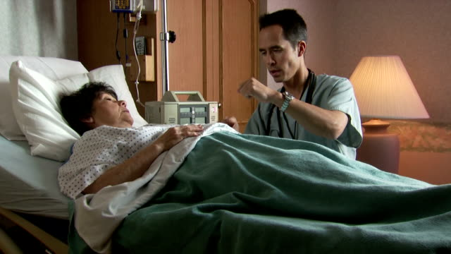 male doctor explaining to mature woman in hospital bed - brechreiz stock-videos und b-roll-filmmaterial