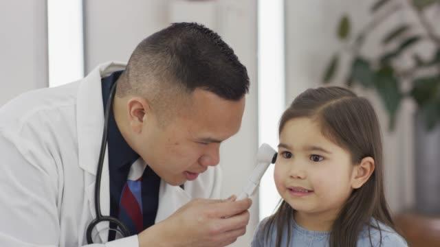 Médecin de mâle à la recherche de jeunes filles oreille